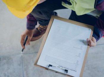 Entre les mains de l'inspecteur se trouve un brouillon de son rapport d'inspection.